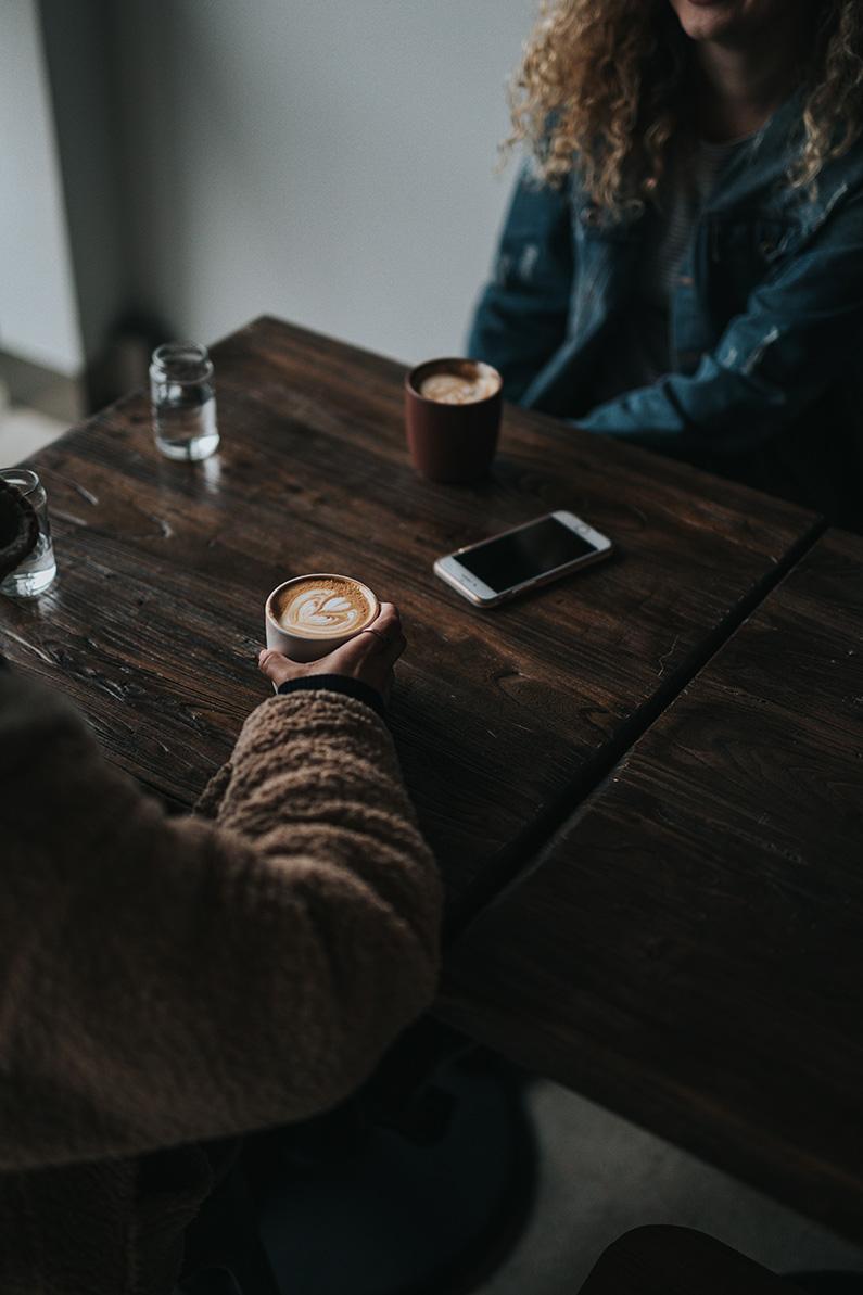 twee mensen drinken koffie iphone ligt op tafel